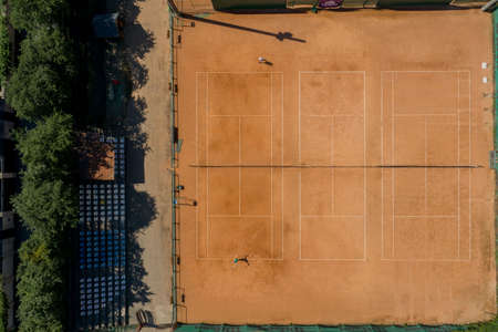 Tennis clay court seen from above with two men playing match. They are mature adult, and very agile and healthy. Video made with drone