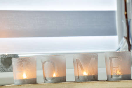 candles with the inscription HOME on the windowsill with beautiful blinds.