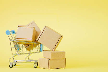 Paper shopping bags in a shopping cart on yellow background, concept online shopping Archivio Fotografico