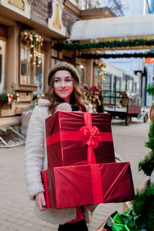 Portrait Happy good-looking woman is holding gift box in her hands and smiling while standing outdoors. Beautiful happy girl posing with Christmas presents. New Year preparation