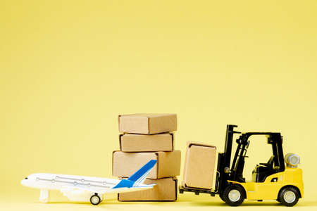 Mini forklift truck load cardboard boxes in the Airplane. Fast delivery of goods and products. Logistics, connection to hard-to-reach places. Banner, copy space.