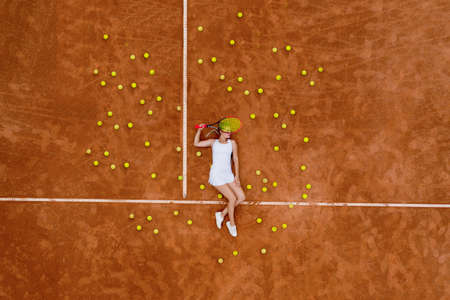 Portrait of smiling girl relaxing on tennis court with a lot of balls and racket after hard tennis trainingg outdoor. Dolly shot. Top view Banque d'images