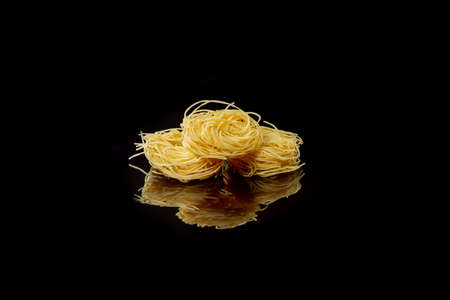 Dry, raw egg pasta capelli, isolated on black background. Cooking concept. Top view with copy space