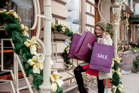 Happy woman holds paperbags with symbol of sale in the stores with sales at Christmas, around the city. Concept of shopping, holidays, happiness, Christmas Sales