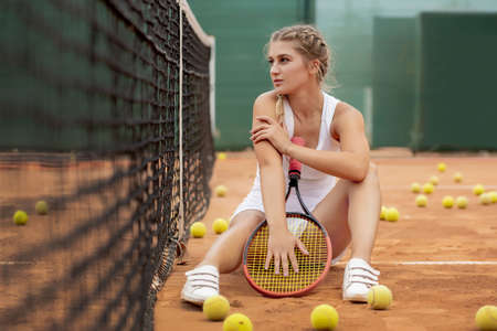 Portrait of beautiful young woman sitting near net in tennis court with ball outdoor. Confident sportswoman resting on tennis court