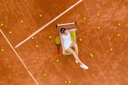 Portrait of smiling woman relaxing on tennis court with a lot of balls and racket after hard tennis trainingg outdoor. Dolly shot. Top view. Banque d'images