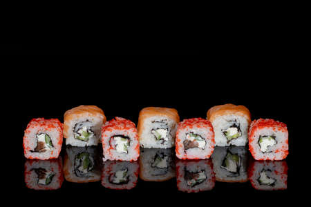 Philadelphia roll with salmon, cheese and cucumber on a black background with reflection. Sushi Philadelphia.