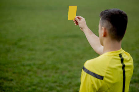 Referee showing a red card to a displeased football or soccer player while gaming. Concept of sport, rules violation, controversial issues, obstacles overcoming