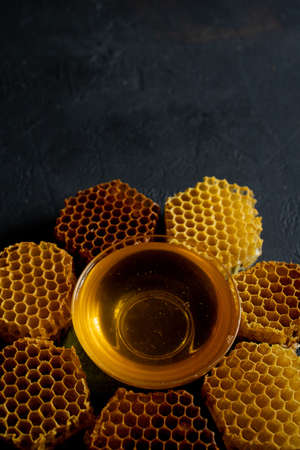 Honey and honeycomb in the form of a flower on black table, top view. space for text. Imagens