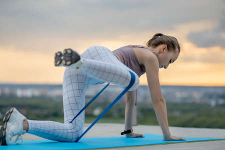 Young attractive woman performing bodyweight fitness training on city background. Beautiful female doing exercises with rubber band. Workout concept