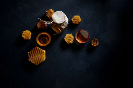 Honey in a jar and a honeycomb. On a black wooden background. Free space for text. Top view Imagens