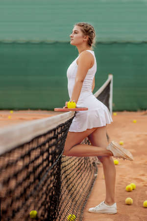 Athletic woman standing near net on court with racket in hands. 版權商用圖片
