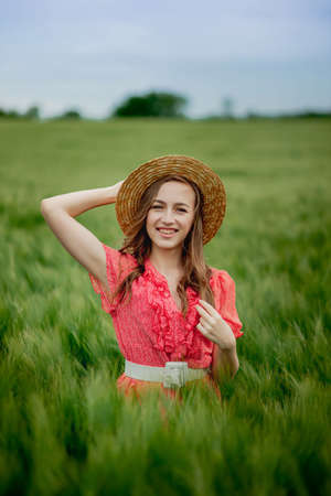 portrait of young woman in dress and hat in green field of barley in countryside. Tranquil rural moment.