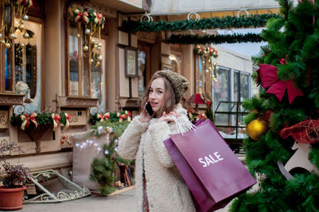 Happy girl holds paperbags with symbol of sale in the stores with sales at Christmas, around the city. Concept of shopping, holidays, happiness, Christmas Sales