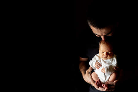 Father holding his 15 days old son in his hand on black background. Baby lying on his father.