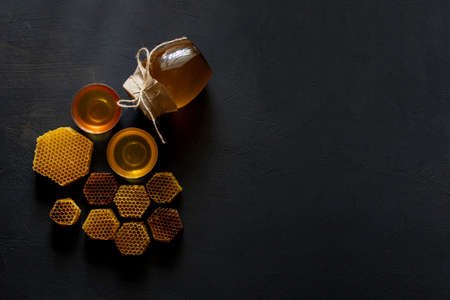 Honey with honeycomb on black table, top view. space for text.