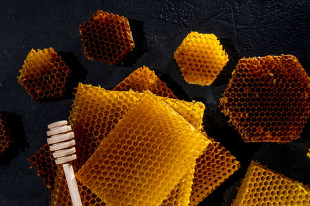 Honey in a jar and a honeycomb. On a black wooden background. Free space for text. Top view 免版税图像