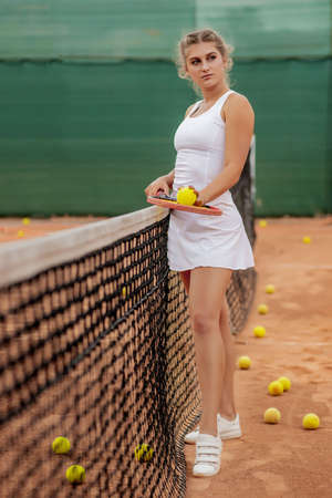 Athletic woman standing near net on court with racket in hands. 免版税图像