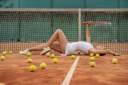 Relaxing after tennis training. Young beautiful girl in white uniform and sporty cap on a tennis court near the net.