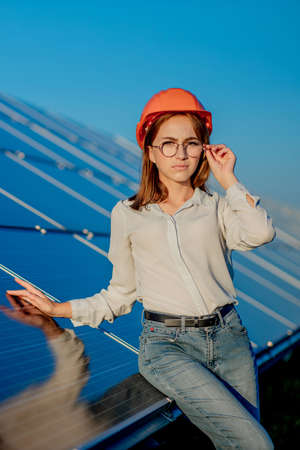 Beautiful young engineer standing near solar panels outdoors, Green Energy Concept. 免版税图像
