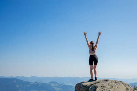 The young woman at the top of the mountain raised her hands up on blue sky background. The woman climbed to the top and enjoyed her success. Back view. 免版税图像