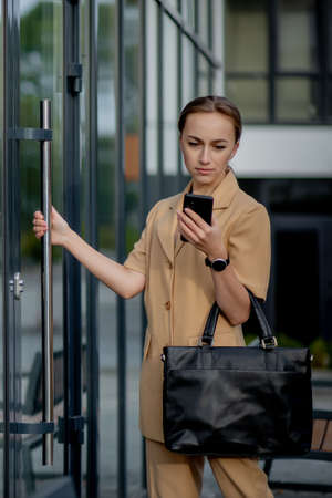 Professional business woman using mobile phone outdoors. Female texting on smart phone while walking outdoor in city