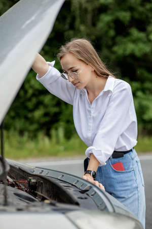 Young woman opening bonnet of broken down car having trouble with her vehicle. Worried woman talking on the phone near broken car. Girl model standing near the broken car calling for auto service.