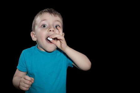 The child puts the pill into his mouth. Close-up Photos.