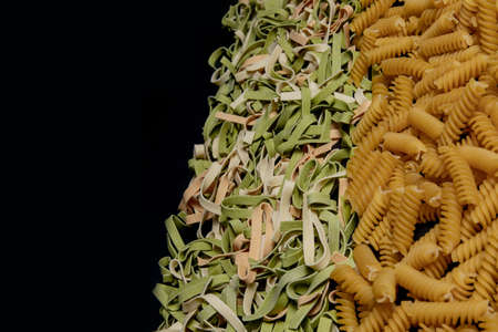 Variety of types and shapes of dry Italian pasta. Italian Macaroni raw food background or texture: pasta, spaghetti, pasta in shape of spiral