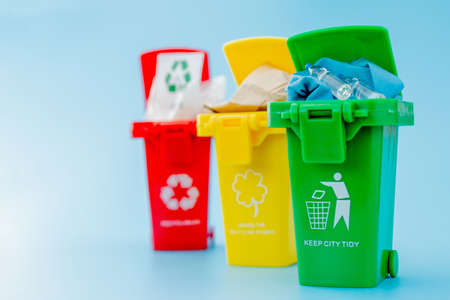 Yellow, green and red recycle bins with recycle symbol on blue background. Keep city tidy, Leaves the recycling symbol. Nature protection concept. 免版税图像