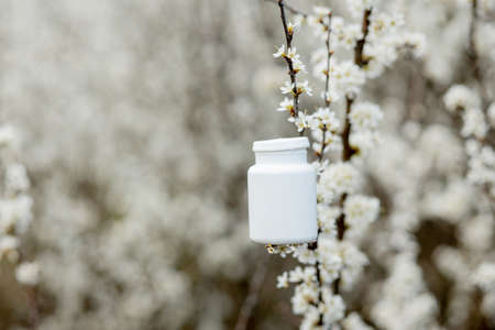 Allergy pills against the blooming plants background.