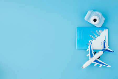 Camera, passport and airplane on light blue background.Summer or vacation concept. Copy space 免版税图像