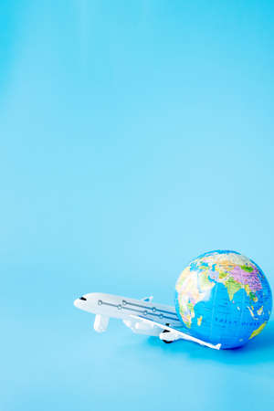 Airplane and globe on blue background. Summer or vacation concept. Copy space.