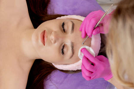 Cosmetologist at spa beauty salon doing acne treatment using mechanical instrument. Concept of medical treatment of rejuvenation and skincare
