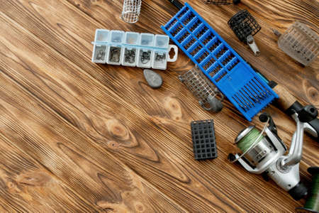 flat lay with fishing tackle, fishing rod and plastic box with fishing tackle and hooks, feeders on wooden planks, copy space.