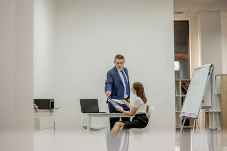 Angry boss yelling at his young employee, she is stressed and feeling frustrated: hostile boss and mobbing concept.