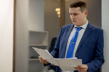 Young businessman working with documents looking through papers in folder, sitting at office desk. Standard-Bild