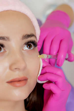 The doctor cosmetologist makes the Rejuvenating facial injections procedure for tightening and smoothing wrinkles on the face skin of a beautiful, young woman in a beauty salon Standard-Bild