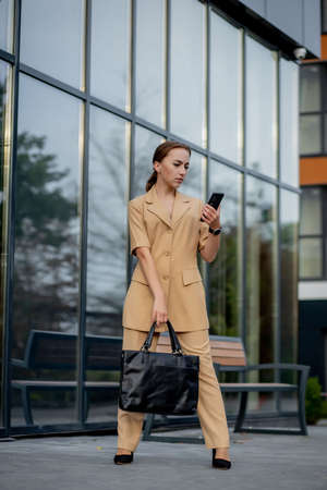Young female executive standing outside office building talking on cell phone. Caucacian businesswoman making a phone call while standing against a corporate office building