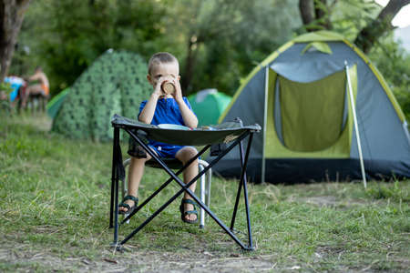Little boy eating breakfast outdoor at camping site in nature sunlight with a tent at the background