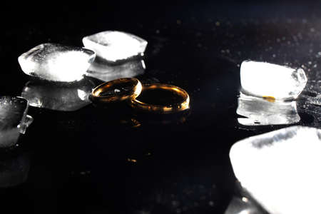 Two golden wedding rings on black background