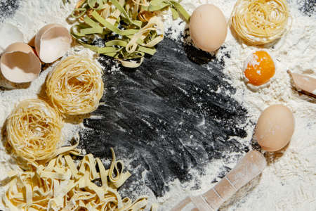 Pasta with ingredients - flour, eggs and different tools for cooking on black table. Free space for text. Top view