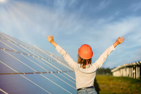 Beautiful young engineer standing near solar panels outdoors, Green Energy Concept. Standard-Bild