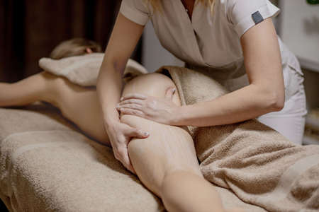 Hands of the massage therapist in the spa salon make massage to a young woman. Concept of care and beauty.massage of buttocks, prevention of cellulitis.