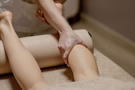 Foot massage in the massage parlor - female hands massage the female feet - beauty and health. Standard-Bild