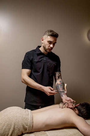 Cupping massage. Young man enjoying back and shouders massage in spa.Professional massage therapist is treating a male patient.Relaxation, beauty, body and face treatment concept.Home massage Standard-Bild