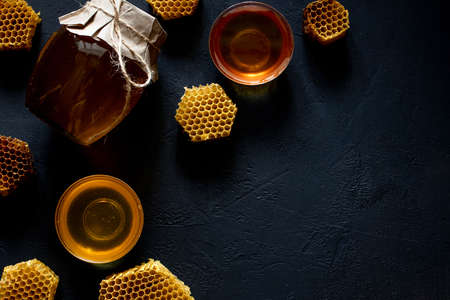 Honey in a jar and a honeycomb. On a black wooden background. Free space for text. Top view Standard-Bild