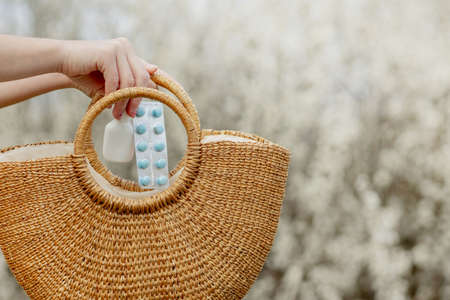 Woman's hand puts allergy pills in bag on blooming background.