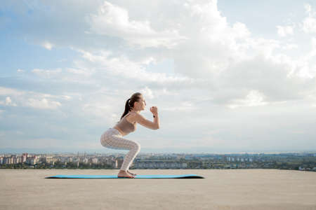 Side view of muscular young woman with long ponytail in sunny morning. Gorgeous girl practicing exercises, warming up lower body on city background. Standard-Bild