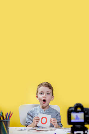 Beautiful little blogger bloging about learning the alphabet on yellow background. Back to school. Distance learning online education